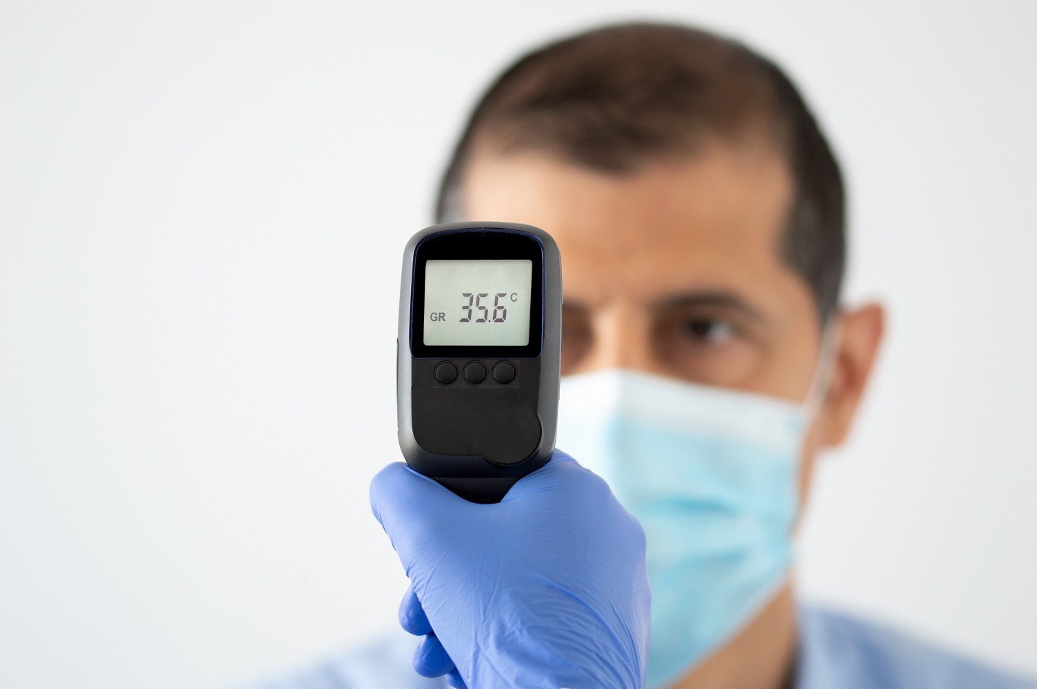 young man getting his temperature taken with an infrared thermometer by a healthcare worker